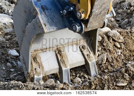 Closeup of the shovel of a digger with part of the hydraulic mechanism