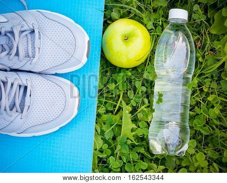 Sneakers on yoga mat bottle of water and apple on fresh green grass. Sports in the open air. Top view