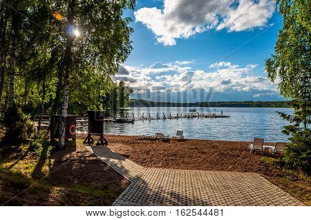 Beautiful deserted sandy beach of a forest lake with sun beds and a pier for fishing in the sun for escape