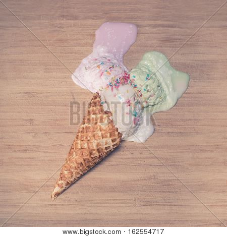 An ice-cream cone with mixed flavours melting on a wooden background. Shot from above.