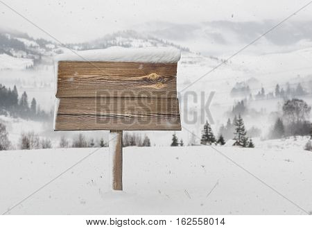 Wooden Signpost With Snow And Mountains
