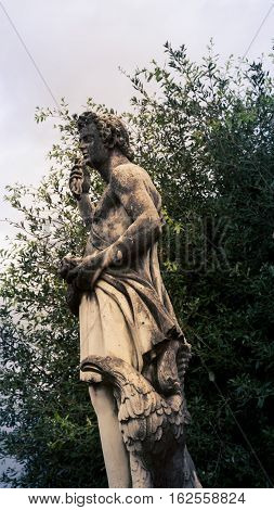 Male robed statue in a park in Florence Italy
