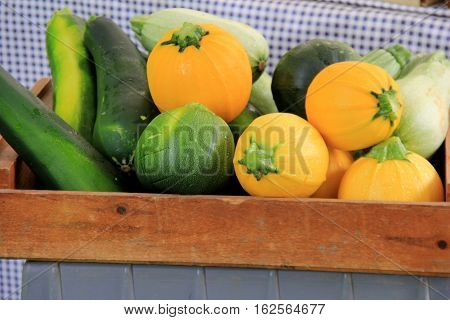 Wood basket on checkered tablecloth, filled with summer squash and zucchini.