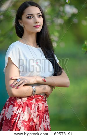Beautiful yong long hair woman wearing luxury accessory in blooming spring garden. Silver bracelet necklace ring on young model girl