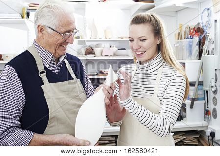 Senior Man With Teacher Looking At Vase In Pottery Class