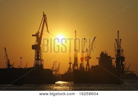 Ship in dry dock and harbor cranes at sunset