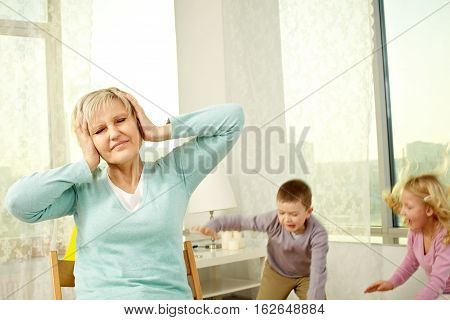 Woman with hands over ears and noisy children behind