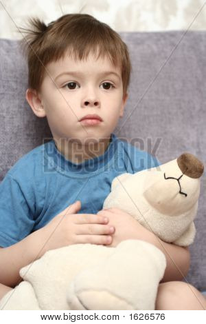 The Sad Boy Holds A Toy In Hands