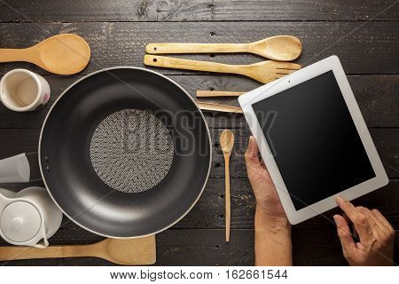 Hand use tablet with kitchenware on black wood tableconcept searching the cooking menu