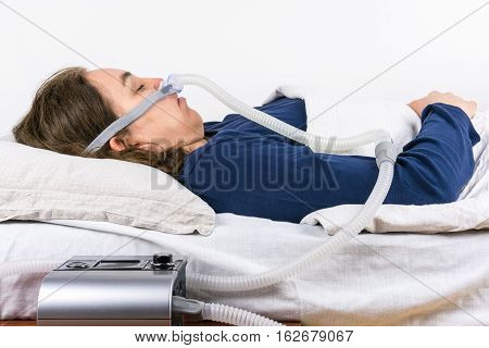 Woman sleeping on her back with CPAP machine in the foreground, sleep apnea treatment. Profile studio shot.
