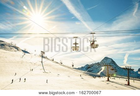 Panoramic view of ski resort on french alps glacier with chair lifts - Winter vacation and sport travel concept - Snowboard season opening and people having fun on mountain - Warm afternoon color tone