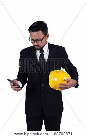 Portrait of a young construction worker using mobile phone isolated on white background