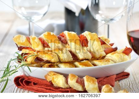 Baked hearty puff pastry sticks with ham and herbs served with a glass of red wine