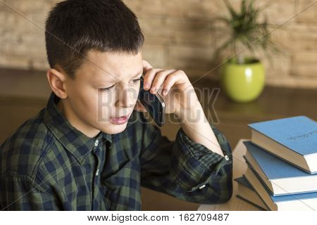 Young Boy Talking On Cell Phone At Home. Mobile Phone Talk Concept.
