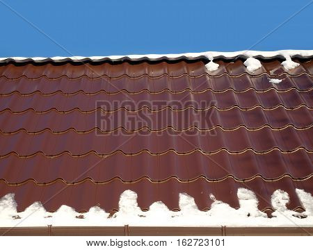 New country house roof from brown metal tile with melting snow in spring under clear cloudless blue sky. Horizontal view closeup