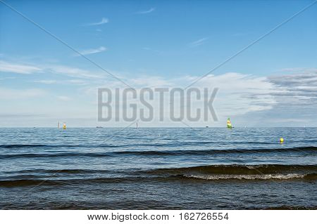 modern yacht or sailing boat or vessel sails by wind on sea water waves surface inshore on blue sky