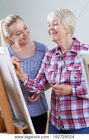 Senior Woman Attending Painting Class With Teacher