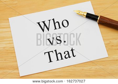 Learning to use proper grammar A white card on a desk with a pen with words Who vs That