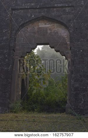 MANDU, MADHYA PRADESH, INDIA - NOVEMBER 19, 2008: Unused entrance to the historic hilltop fortress town of Mandu in Madhya Pradesh, India. The fortifications originated in the 10th century AD.