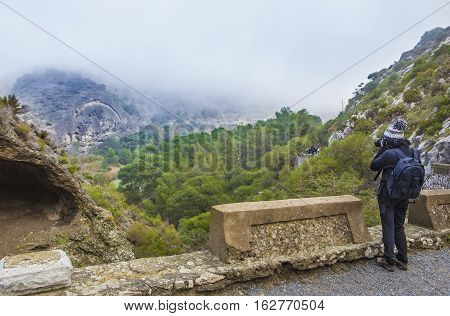 One trekker woman walking along the Caminito del Rey path Malaga Spain. She is taking pictures with reflex camera