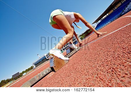 Female athlete standing on starting line ready to run