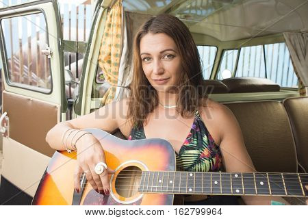 A young woman poses with her guitar in the backseet of her combi van.