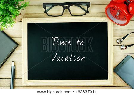 Top view of earphone, calculator, alarm clock, spectacle, notebook, pen, smartphone and chalkboard written with TIME TO VACATION.
