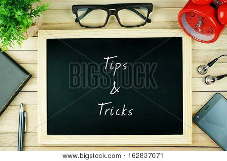 Top view of earphone, calculator, alarm clock, spectacle, notebook, pen, smartphone and chalkboard written with TIPS AND TRICKS.