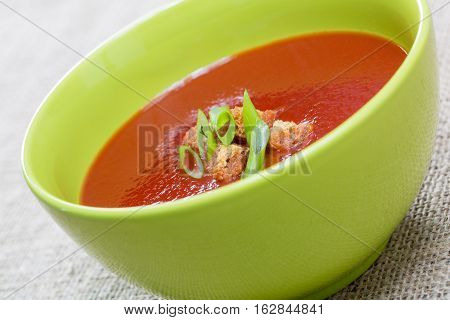 Close Up Of Tomato Soup With Bread Crumbs And Green Onions