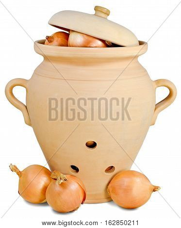 ceramic pitcher for storing vegetables in brown colour with three holes and covered with a lid with three heads of onions lying next to the jug on the table isolated on white background