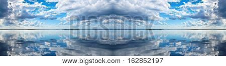 Spectacular blue and white panoramic cloudscape with clear water reflections. Photgraph was shot at sea from the deck of a boat looking toward land.