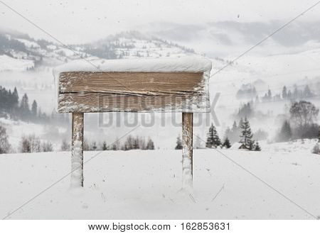 Wide wooden signpost with snow on it and snowfall and mountains on background