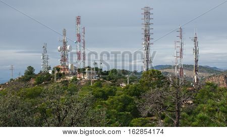 Detailed view of communication towers over cloudy sky on top of mountain