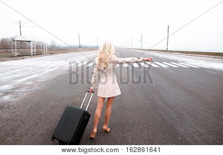 Girl In Coat With Suitcase Hitchhiking On The Winter Road, Trip And Travel Concept