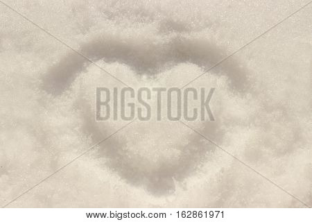 Lost love illustrated by the imprint of a heart in the snow