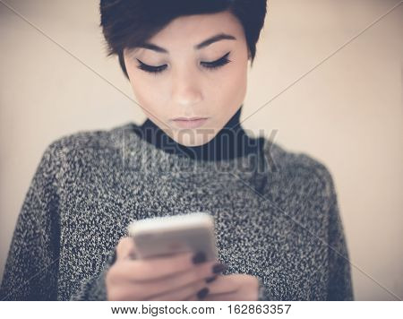 Young teen girl portrait absorbed using and writing mobile phone
