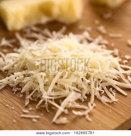 Freshly grated parmesan-like hard cheese on wooden board photographed with natural light (Selective Focus Focus in the middle of the image)