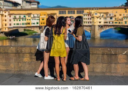 Young Asian Women Taking Photos On The Ponte Trinita In Florence, Italy
