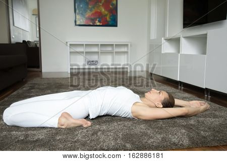 Attractive young woman practicing yoga, lying in Reclining Hero exercise, Virasana pose, working out, wearing white sportswear, indoor full length, home interior background