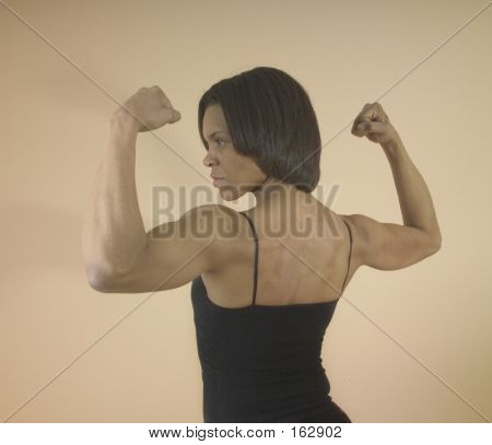 Strong Woman Flexing Her Arm Muscles | Stock photo. download preview