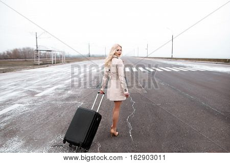Hitchhiking Tourism Concept. Portrait Of Travel Hitchhiker Woman In Fur Coat Walking On Road
