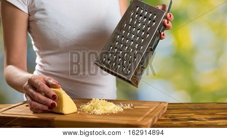 Girl preparing sauce for pasta and grating cheese