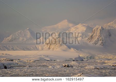 Mountains covered with snow and glaciers of the Antarctic Peninsula a small snow storm