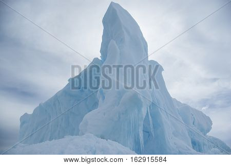 tip of the iceberg on a background cloudy sky in the Antarctic winter day
