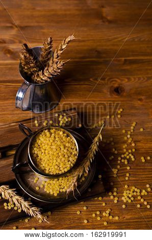 Dry round pasta on the wooden background. Selective focus.