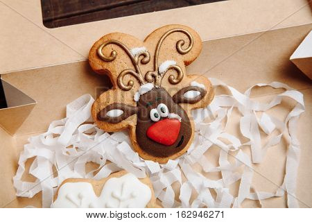 Craft box with Christmas homemade gingerbread cookies with reindeer Ralph on wooden table