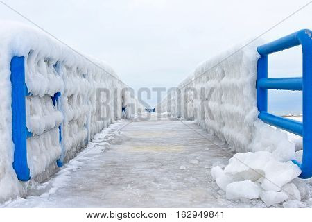 ice formation on pier with blue railings in Lake Michigan