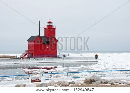 red lighthouse on Lake Michigan in winter