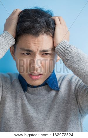 man feel headache with blue background asian