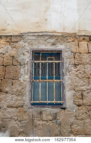 and old blue wooden window behind metal gratings